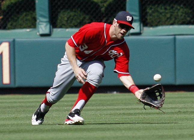 Washington Nationals' Bryce Harper fields a fly ball hit by Philadelphia Phillies'  Erik Kratz for an out in the fifth inning of a baseball game on Sunday, Aug. 26, 2012, in Philadelphia. The Phillies won 4-1. (AP Photo/H. Rumph Jr)