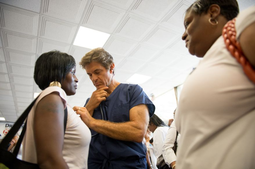 Joyce Carey, right, of Washington, D.C., watches as Dr. Mehmet Oz, host of The Dr. Oz Show listens to Dakeia's heart, left, during a 15-minute clinic open to the public with the help of Howard University medical students to get a very basic idea of people's general risk for heart disease and diabetes at Howard University in the District on Wednesday, Sept. 5, 2012. (Andrew Harnik/The Washington Times)