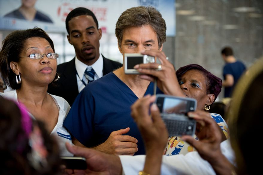 People crowd Dr. Mehmet Oz, host of The Dr. Oz Show to take photos with him as he hosts a 15-minute clinic open to the public with the help of Howard University medical students to get a very basic idea of people's general risk for heart disease and diabetes at Howard University in the District on Wednesday, Sept. 5, 2012.