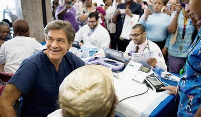 Dr. Mehmet Oz, host of The Dr. Oz Show sits down to go through the exam of Gladys Nealy of Washington, D.C. during a 15-minute clinic open to the public with the help of Howard University medical students to get a very basic idea of people's general risk for heart disease and diabetes at Howard University in the District on Wednesday, Sept. 5, 2012. (Andrew Harnik/The Washington Times)