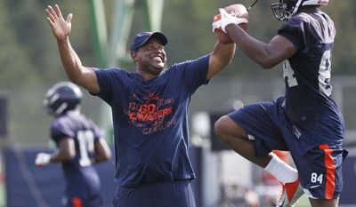 In this Aug. 6, 2012, photo, Virginia coach Mike London congratulates wide receiver Canaan Severin (84) on a catch during the NCAA college football team's practice in Charlottesville, Va. (AP Photo/The Daily Progress, Sabrina Schaeffer)