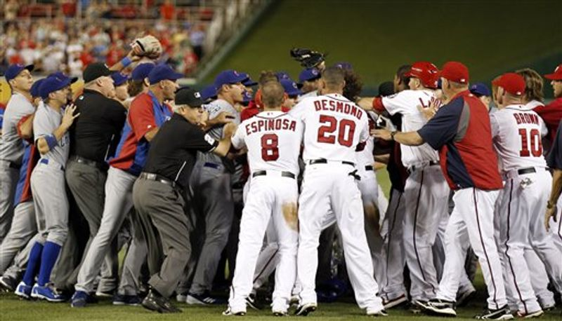 Umpires try to restore order during the sixth inning when both benches and bullpens emptied onto the field of a baseball game between the Washington Nationals and the Chicago Cubs at Nationals Park, Thursday, Sept. 6, 2012, in Washington. The Nationals won 9-2. (AP Photo/Alex Brandon)
