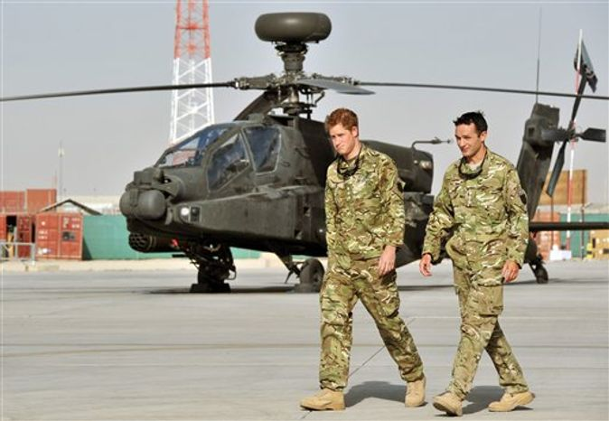 Britain's Prince Harry is shown the Apache flight-line, Friday, Sept. 7, 2012, by a member of his squadron (name not provided) at Camp Bastion in Afghanistan, where he will be operating from during his tour of duty as a co-pilot gunner. Prince Harry, also known as Capt. Harry Wales, has returned to Afghanistan to fly attack helicopters in the fight against the Taliban. (AP Photo/ John St