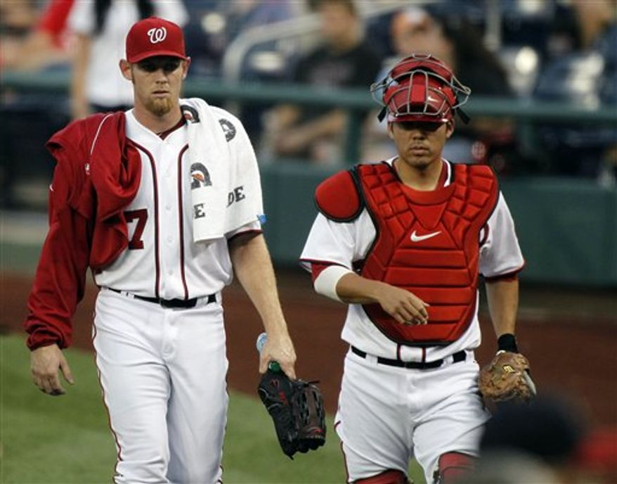 Washington Nationals starting pitcher Stephen Strasburg, left, walks to the dugout with catcher Kurt Suzuki before a baseball game against the Miami Marlins at Nationals Park Friday, Sept. 7, 2012, in Washington. (AP Photo/Alex Brandon)