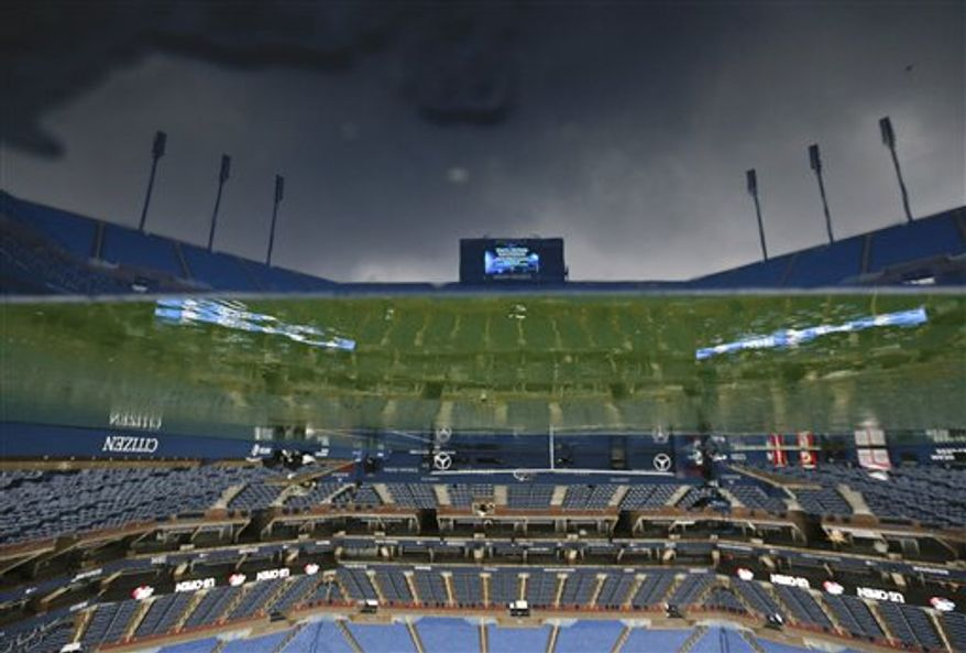 The tennis court at Arthur Ashe stadium is shown as rain falls before play is to resume at the 2012 US Open tennis tournament, Saturday, Sept. 8, 2012, in New York. (AP Photo/Charles Krupa)