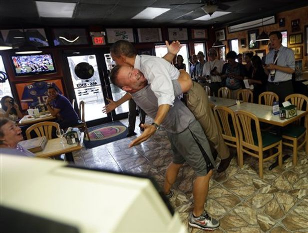 President Obama is lifted off the ground by Scott Van Duzer, owner of Big Apple Pizza and Pasta Italian Restaurant, on Sept. 9, 2012, during an unannounced stop at the restaurant in Ft. Pierce, Fla. (Associated Press)