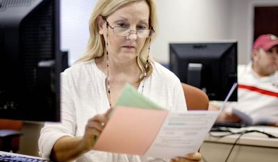 Judy Smith of Dalton, Ga., looks over paperwork as she files for unemployment for the first time since being laid off from a catering job. Though the unemployment rate dropped to 8.1 percent in August, pushed down by 368,000 dropping out of the labor force, job growth remains subpar and will not be enough to put millions back to work. (Associated Press)
