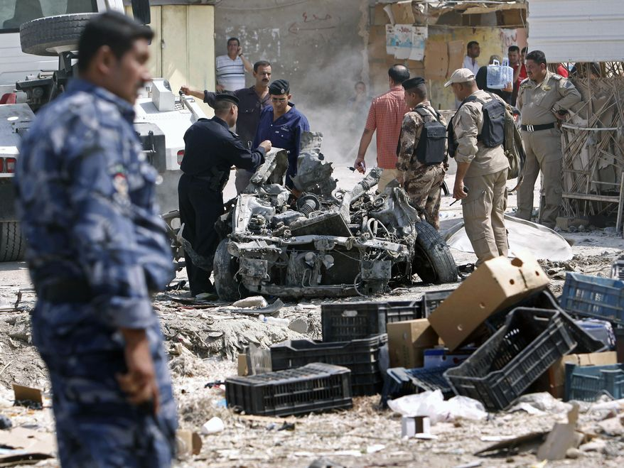 Security forces inspect the scene of a car bombing in Basra, Iraq, 340 miles southeast of Baghdad, on Sunday, Sept. 9, 2012. (AP Photo/Nabil al-Jurani)