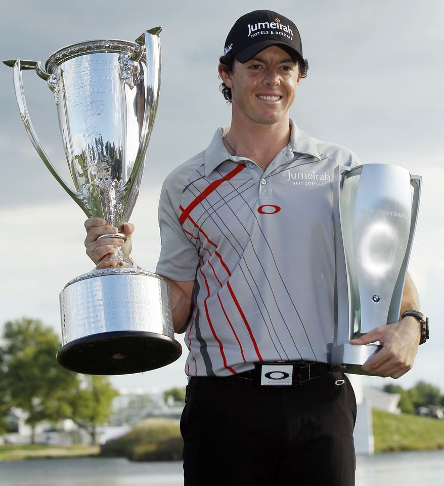 Rory McIlroy, of Northern Ireland, holds the Western Golf Association's J.K. Wadley trophy, left, and the BMW trophy after winning the BMW Championship PGA golf tournament at Crooked Stick Golf Club in Carmel, Ind., Sunday, Sept. 9, 2012. (AP Photo/Charles Rex Arbogast)
