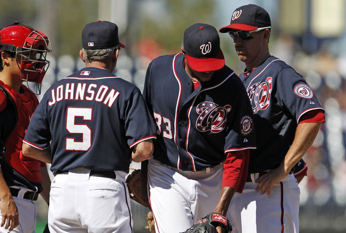 Washington Nationals manager Davey Johnson (5) relieves pitcher Edwin Jackson, second from right, with catcher Kurt Suzuki and first baseman Adam LaRoche, right, also standing on the mound during the fifth inning o