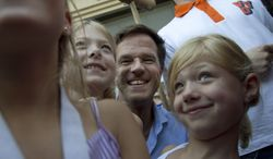Dutch Prime Minister Mark Rutte poses with children during a campaign visit in Dordrecht, Netherlands, on Saturday, Sept. 8, 2012, four days ahead of national elections. (AP Photo/Peter Dejong)