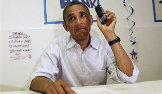 President Obama uses a cellphone to contact supporters during a surprise visit to meet volunteers at an Obama campaign office in Port St. Lucie, Fla. on Sept. 9, 2012. (Associated Press) **FILE**