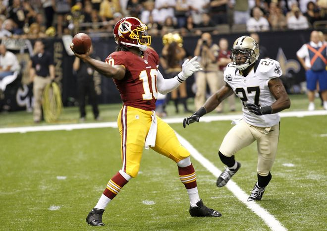 Washington Redskins quarterback Robert Griffin III (10) throws a touchdown pass under pressure from New Orleans Saints free safety Malcolm Jenkins (27) in the first quarter of an NFL football game at Mercedes-Benz Superdome in New Orleans, Sunday, Sept. 9, 2012. (AP Photo/Bill Haber)