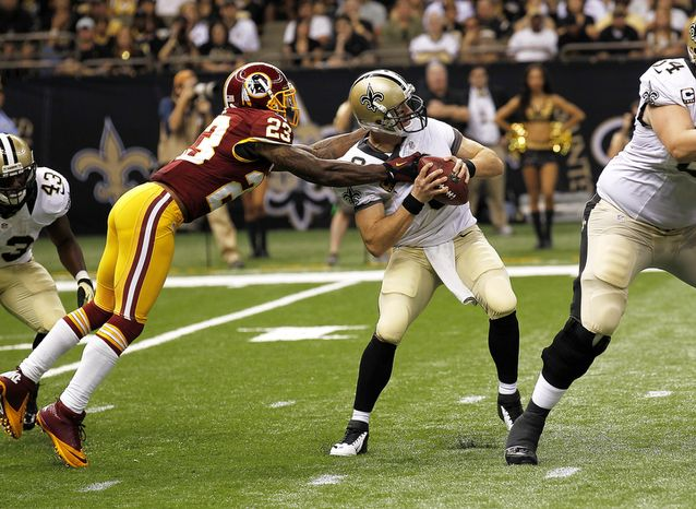 New Orleans Saints quarterback Drew Brees (9) is sacked by Washington Redskins cornerback DeAngelo Hall (23) in the first half of an NFL football game at the Mercedes-Benz Superdome in New Orleans, Sunday, Sept. 9, 2012. (AP Photo/Bil