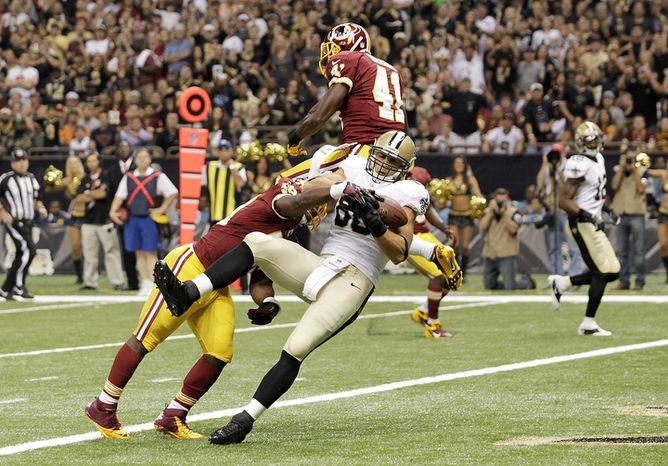 New Orleans Saints tight end Jimmy Graham (80) pulls in a touchdown pass over Washington Redskins defensive back Madieu Williams (41) in the first half of an NFL football game at the Mercedes-Benz Superdome in New Orleans, Sunday, Sept. 9, 2012. (AP Photo/Matthew Hinton)