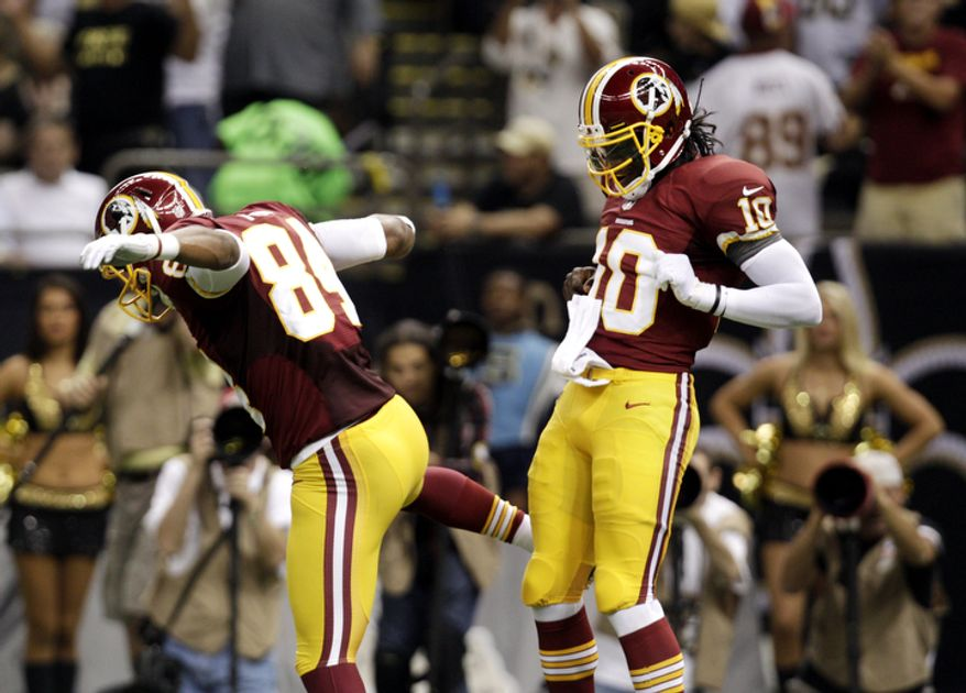Washington Redskins quarterback Robert Griffin III (10) celebrates a touchdown with tight end Niles Paul (84) in the first half of an NFL football game at the Mercedes-Benz Superdome in New Orleans, Sunday, Sept. 9, 2012. (AP Photo/Matthew Hinton)