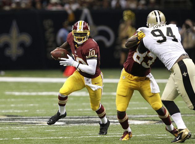 Washington Redskins quarterback Robert Griffin III (10) around New Orleans Saints defensive end Cameron Jordan (94) in the second half of an NFL football game at the Mercedes-Benz Superdome in New Orleans, Sunday, Sept. 9, 2012. (AP Photo/Matthew Hinton)