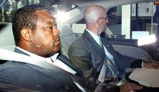 In this 2012 file photo, then-Trenton, N.J., Mayor Tony Mack (left) is driven to the federal courthouse in the capital after agents arrested him as part of an ongoing corruption investigation into bribery allegations related to a parking garage project that was concocted as part of an FBI sting operation. (Associated Press)