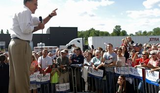 GOP presidential hopeful Mitt Romney stands atop a makeshift stage Monday as he addresses an overflow crowd at PR Machine Works in Mansfield, Ohio. (Associated Press)