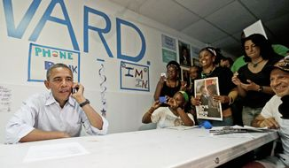 President Obama uses a cellphone to contact supporters during a surprise visit to meet campaign workers at an Obama campaign office Sunday in Port St. Lucie, Fla. Florida is considered the biggest prize among the swing states up for grabs. (Associated Press)