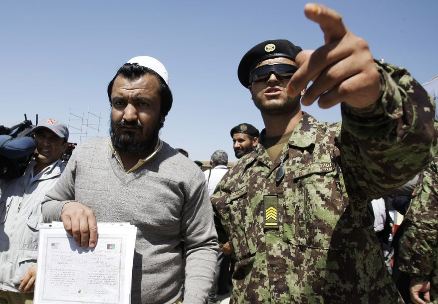 An Afghan soldier (right) escorts a released prisoner, Mohammad Karim, following a ceremony on Sept. 10, 2012, marking the handover of a U.S.-run prison to Afghan government in Bagram, Afghanistan. (Associated Press)
