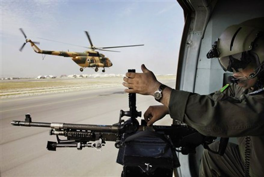 An Afghan soldier adjusts bullets in his gun Sept. 10, 2012, on a military helicopter during a flight transporting journalists from Kabul, Afghanistan, to Bagram. The journalists were to attend a ceremony where U.S. officials handed over formal control of the country's only large-scale U.S.-run prison to Afghanistan. (Associated Press)