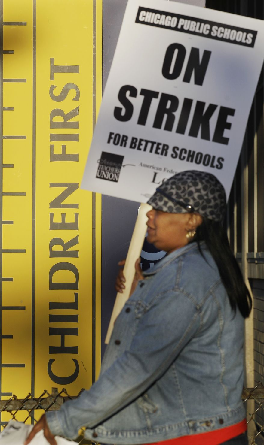 Chicago teacher Alma Hill walks a picket line Sept. 10, 2012, outside Benjamin Banneker Elementary School after city teachers went on strike for the first time in 25 years. Union and district officials failed to reach a contract agreement despite intense weekend negotiations. (Associated Press)