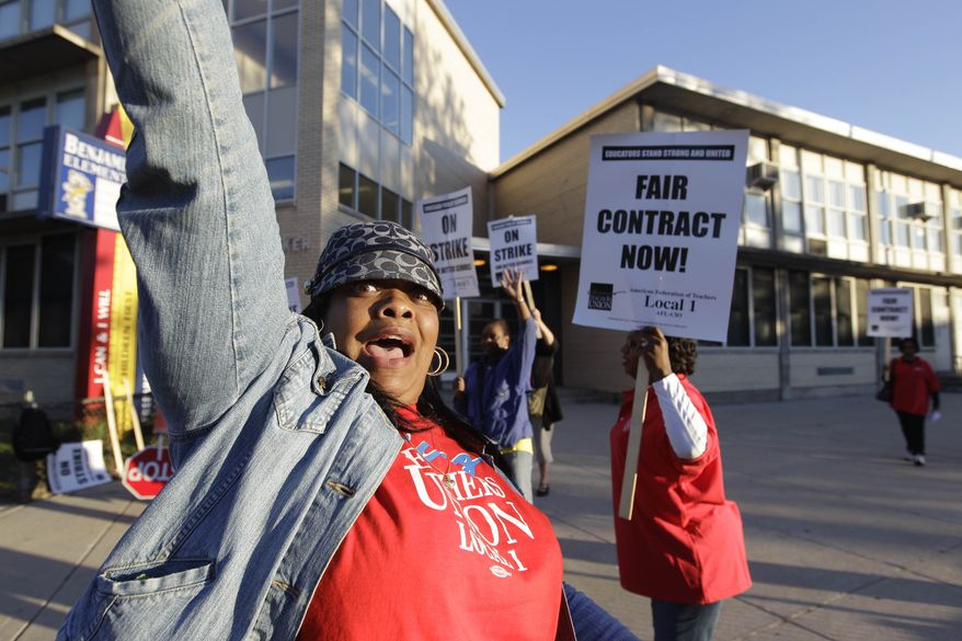 Chicago teachers walk a picket line outside Benjamin Banneker Elementary School in Chicago on Sept. 10, 2012, after they went on strike for the first time in 25 years. Union and district officials failed to reach a contract agreement despite intense weekend negotiations. (Associated Press)