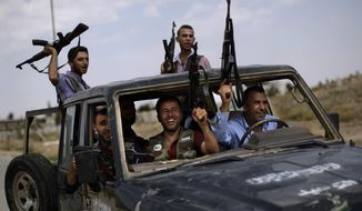 Syrian rebel fighters raise their weapons Sept. 10, 2012, as they head to fight government forces in Suran, Syria, on the outskirts of Aleppo. (Associated Press)