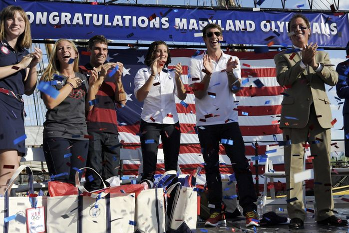 Olympic swimmer Michael Phelps, second from right, joins other Olympic athletes from Maryland, including swimmer Katie Ledecky, left, windsurfer Farrah Hall, second from left, and modern pentathlete Suzanne Stettinius, third from right, and Baltimore County Executive Kevin Kamenetz, right, during a celebration of the achievements of Maryland Olympians, Monday, Sept. 10, 2012, in Baltimore. Phelps ended his Olympic career in London with six medals and a record tally of 22 career medals. (AP Photo/Steve Ruark)
