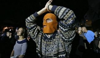 A masked spectator reacts Sept. 9, 2012, during a concert in St. Petersburg, Russia, organized to support jailed Pussy Riot musicians. A Moscow judge has sentenced each of three members of the provocative punk band to two years in prison on hooliganism charges following a trial that has drawn international outrage as an emblem of Russia's intolerance to dissent. (Associated Press)