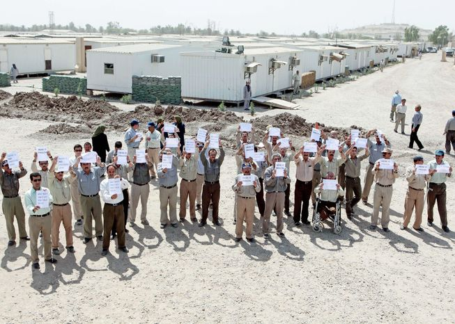 Camp Liberty residents, Iranian dissidents given refuge by Saddam Hussein years ago, hold banners and chant during a tour for foreign diplomats given by the Iraqi government. They want to return to their previous home, Camp Ashraf, but the Iraqi government wants them out of the country. (Associated Press)