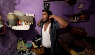 Pradeep Kumar puts on his security guard uniform as he gets ready to go to work at the Deen Dayal Upadhyay Hospital in New Delhi on Monday, Aug. 20, 2012. (AP Photo/Manish Swarup)