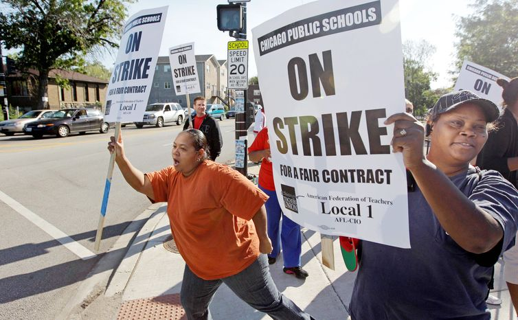 Carmen Brownlee (left) and Latonya Williams, parents of Chicago public school students, walk a picket line with striking teachers Tuesday. The teachers union said it had signed off on just six of 48 articles in the contract under negotiation. Issues in the bitter dispute include teacher evaluations and job security. (Associated Press)