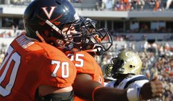 Virginia running back Kevin Parks (25) celebrates a touchdown with teammate  Luke Bowanko (70) during the first half of an NCAA college football game at Scott stadium  in Charlottesville, Va., Saturday, Oct. 15, 2011. (AP Photo/Steve Helber)