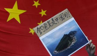 "A protester demonstrating against Japan's claim to disputed islands holds a picture of the rocky islands, known as Senkaku to Japanese and Diaoyu to Chinese, on Sept. 11, 2012 in front of a Chinese national flag during a rally outside the Japanese Consulate General in Hong Kong. The sign reads ""Diaoyu belongs to China."" (Associated Press)"