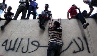 Egyptian protesters climb the walls of the U.S. Embassy during a protest in Cairo on Tuesday, Sept. 11, 2012. (AP Photo/Nasser Nasser)