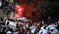 **FILE** Egyptian protesters climb the walls of the U.S. Embassy in Cairo on Sept. 11, 2012. The protesters, largely ultraconservative Islamists, went into the courtyard and brought down the U.S. flag, replacing it with a black flag with Islamic inscription, in protest of a film deemed offensive of Islam. (Associated Press)
