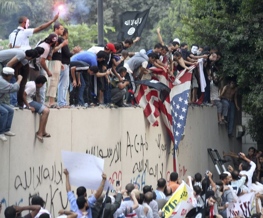 Protesters destroy an American flag pulled down from the U.S. embassy in Cairo on Sept. 11, 2012. The protesters, largely ultraconservative Islamists, climbed the walls of the embassy, went into the courtyard and brought down the flag, replacing it with a black flag with Islamic inscription, in protest of a film deemed offensive of Islam. (Associated Press)