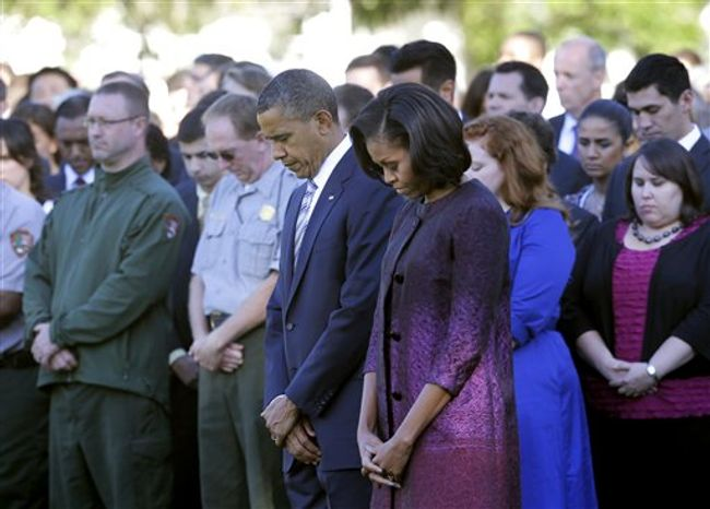 President Obama, first lady Michelle Obama and members of the White House staff pause Sept. 11, 2012, on the South Lawn of the White House in Washington during a moment of silence to mark the 11th anniversary of the terrorist attacks. (Associated Press)