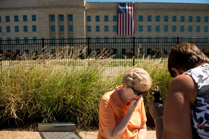 Marlene Menke, of Cedar Rapids, Iowa, center, wipes tears from her eyes as she and her sister-in-law Carolyn Menke, right, listen to an audio recording about the Sept. 11th attacks on the 11th anniversary at the Pentagon 9/11 Memorial, Arlington, Va., Tuesday, Sept. 11, 2012. (Andrew Harnik/The Washington Times)