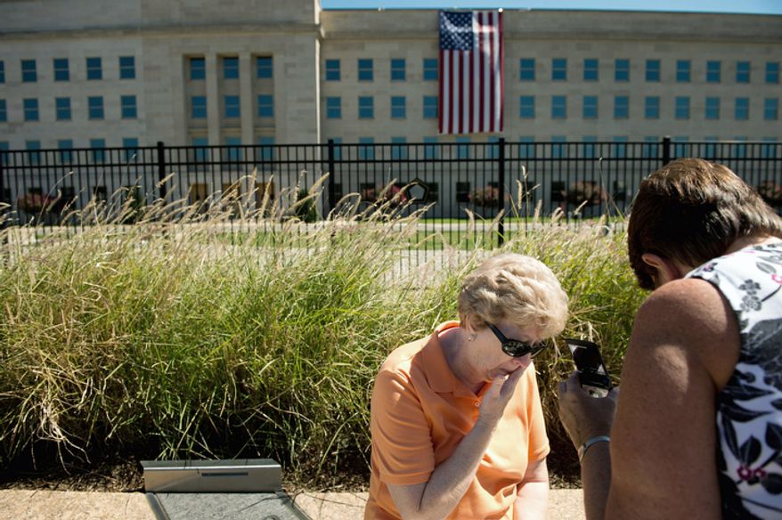 Marlene Menke (center) of Cedar Rapids, Iowa, wipes tears from her eyes as she and her sister-in-law Carolyn Menke (right) listen to an audio recording about the Sept. 11 attacks on the 11th anniversary of 9/11 at the Pentagon 9/11 Memorial. (Andrew Harnik/The Washington Times)