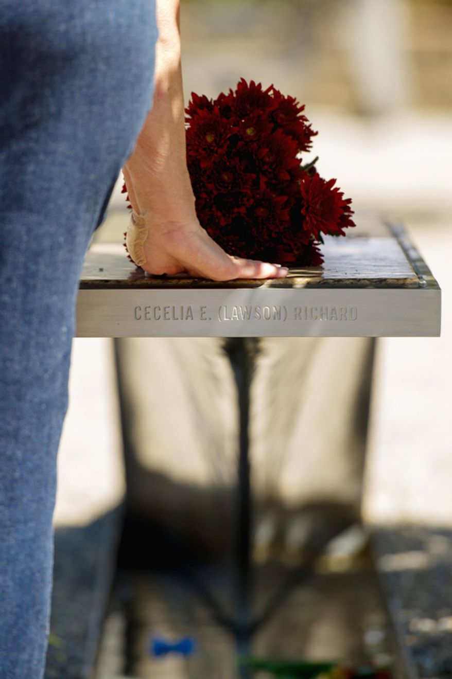 Deborah Hudson of Alexandria touches the memorial bench of her friend Cecilia Richards after leaving a bouquet of red flowers on the 11th anniversary of 9/11 at the Pentagon 9/11 Memorial. (Andrew Harnik/The Washington Times)