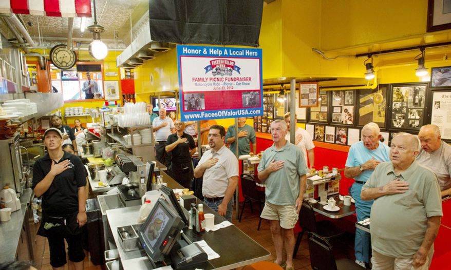 Led by Chuck Munyon (not pictured) of Annapolis, servers, cooks and customers stand during the Pledge of Allegiance at Chick and Ruth's Delly in Annapoli on Tuesday, Sept. 11, 2012. The pledge has been said daily since 1989. (Rod Lamkey Jr./The Washington Times)