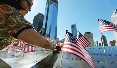 Frances Mercado and her husband, Rafael Mercado Jr. (not seen), visit the engraved name of her sister, Myrna T. Maldonado-Agosto, who died during the Sept. 11 attack, during the commemoration ceremony of the 11th anniversary of 9/11. (AP Photo/The New York Times, Chang W. Lee, Pool)