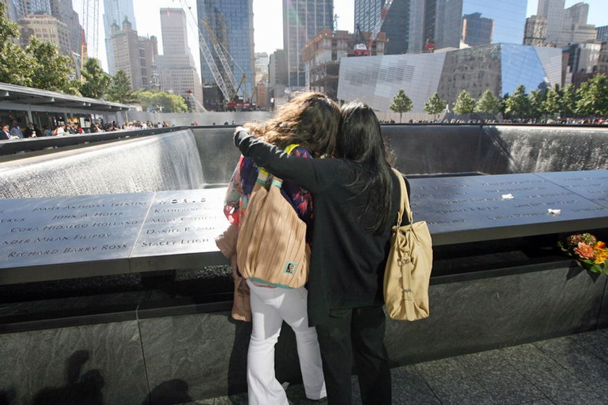 Tania Garcia of Florida, who lost her sister Marlyn Garcia during the Sept. 11 terrorist attacks, comforts Cathy Pepe of Yorktown Heights, N.Y., who lost her husband, Salvatore, during the attacks, during a ceremony marking the 11th anniversary of 9/11 at the National Sept. 11 Memorial at the World Trade Center site in New York. (AP Photo/The Record of Bergen County, Chris Pedota, Pool)