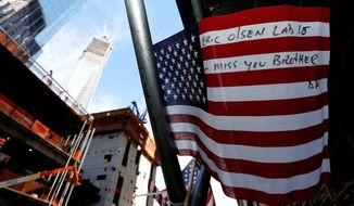 A message is written on a United States flag at the construction site of One World Trade Center in the background during the 11th anniversary of the Sept. 11 terrorist attacks. (Associated Press)