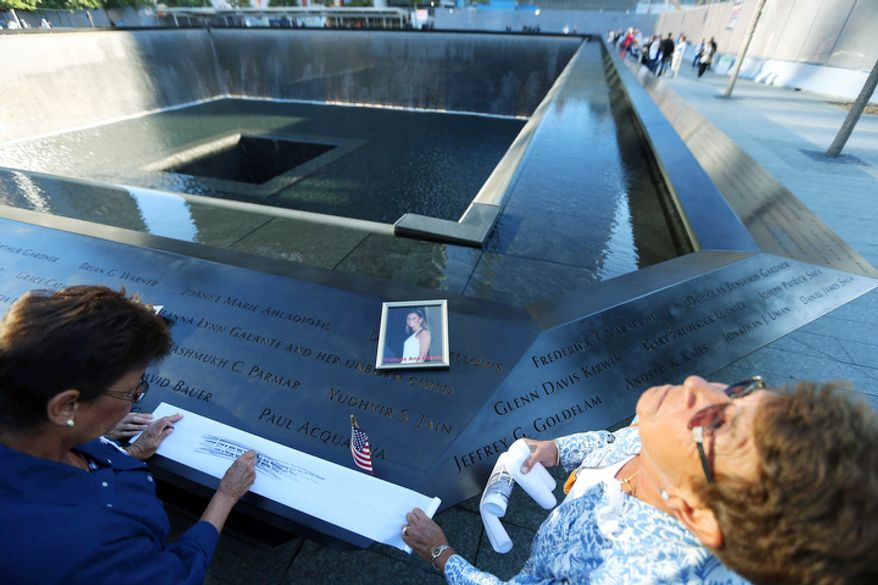 Judy Parisio (right) looks up as she and Linda Malbrba (left) make a copy of the engraved name of their niece, Frances Ann Cilente, who worked and died at the World Trade Center, as the giant flag came down at One World Trade Center during the commemoration ceremony of the 11th anniversary of 9/11. (AP Photo/The New York Times, Chang W. Lee, Pool)