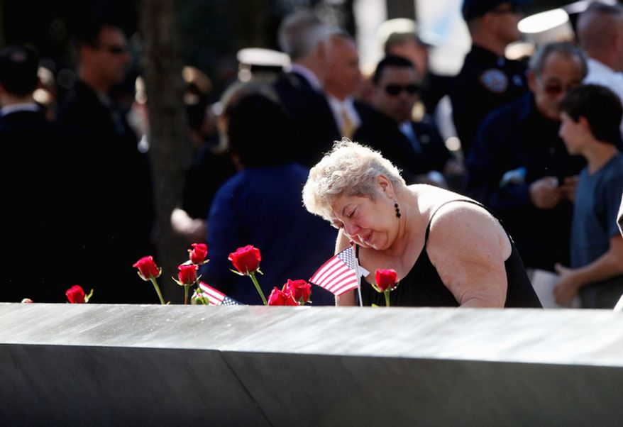 Geraldine Shaw of East Windsor, N.J. looks at the name of her son Jeffrey on a panel of the north pool during a ceremony marking the 11th anniversary of the Sept. 11 terrorist attacks at the National Sept. 11 Memorial at the World Trade Center site. (AP Photo/The Record of Bergen County, Chris Pedota, Pool)