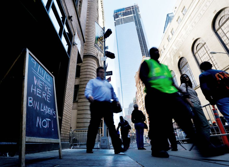People walk pass a sign in front of Trinity Boxing Club with the construction site of Four World Trade Center at their backs during the 11th anniversary of the Sept. 11 terrorist attacks. (AP Photo/Julio Cortez)
